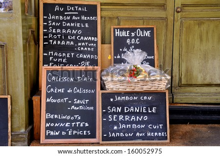 Advertisement board at a French grocery.The text tells the people in French that they sell various kinds of ham, oil and other things.