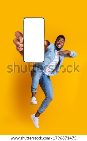 Advertisement for mobile application. Excited african guy dancing over yellow background, showing modern smartphone with empty screen, collage