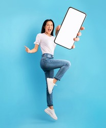 Advertisement for mobile application. Excited young lady jumping over blue studio background, showing modern smartphone with empty screen, mockup for app. Collage