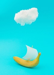 Advertisement idea with a cloud, yellow banana like a ship and a sail of paper against pastel blue background. Minimal summer nature concept in vertical orientation.