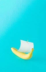 Advertisement idea with a yellow banana like a ship and a sail of paper against pastel blue background. Minimal summer nature concept in vertical orientation.