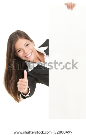 Advertisement woman holding sign. Businesswoman in suit giving thumbs up success sign and showing blank white billboard sign. Mixed race Chinese Asian / Caucasian woman isolated on white background.