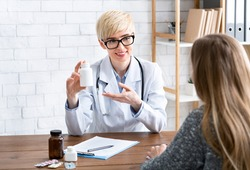 Advertising and pharmacology concept. Female doctor holds jar of medicine in hands and offers patient