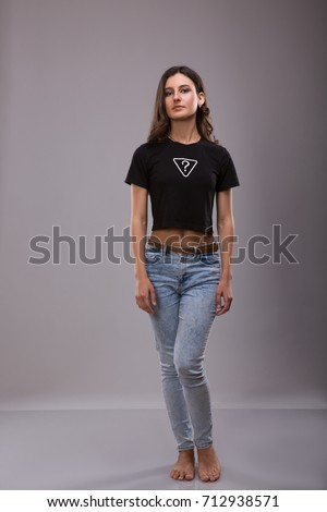 Advertising and T-shirt design concept. portrait of stylish woman wearing black T-shirt with inscription questoin mark and blue jeans standing against gray studio wall with copy space  Stock photo ©