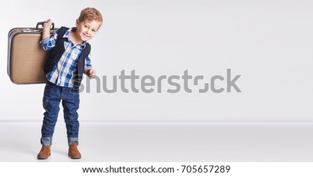 Advertising banner Little boy standing with a suitcase in hand, goes on vacation. Old suitcase and a baby. Business boy, cheerful, active child. Journey. Isolate