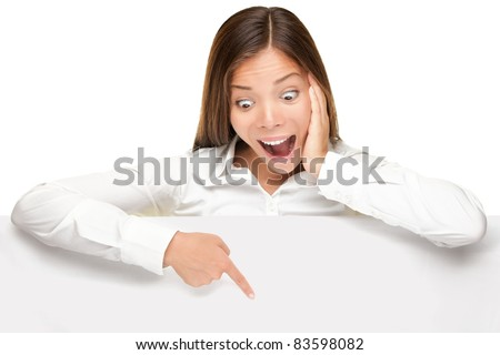 advertising banner sign - woman excited pointing looking down on empty blank billboard paper sign board. Young business woman isolated on white background.
