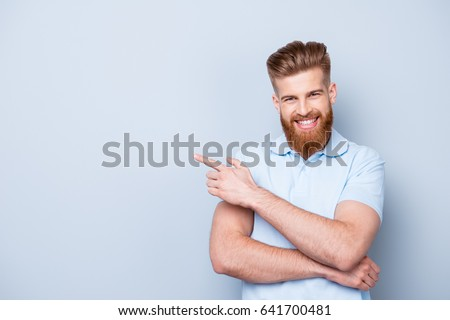 Advertising barber shop concept. Young handsome red bearded stylish guy is pointing on a copyspace on pure light background