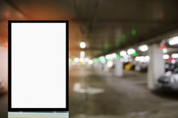 advertising billboard or blank showcase light box for your text message or media content with blurred image of intelligent car parking garage, commercial and marketing concept