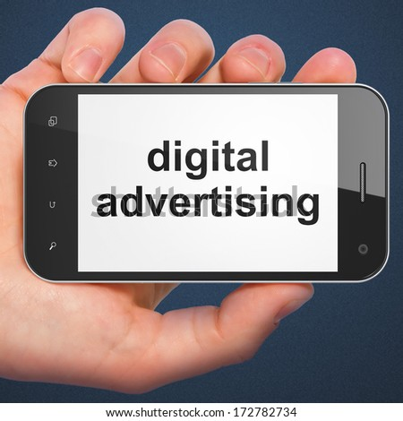 Advertising concept: hand holding smartphone with word Digital Advertising on display. Mobile smart phone on Blue background, 3d render