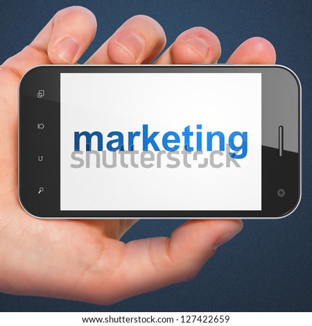 Advertising concept: hand holding smartphone with word Marketing on display. Generic mobile smart phone in hand on Dark Blue background.