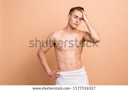 Advertising concept. Handsome man with hand in clean hair, towel, naked torso standing isolated on pastel beige background