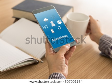 Advertising concept. Man viewing ads on mobile phones while drinking coffee on the desk in the morning. #507001954