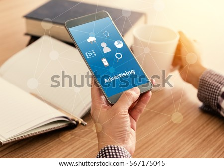 Advertising concept. Man viewing ads on mobile phones while drinking coffee on the desk in the morning. #567175045