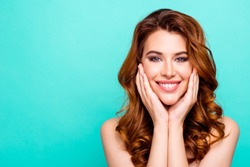Advertising concept. Portrait of young woman with big toothy smile, modern curly ginger hairdo, enjoying her perfect skin after cream, lotion, peeling isolated on vivid turquoise background
