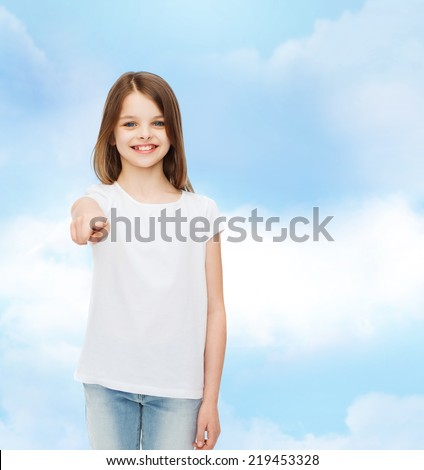 advertising, dream, childhood, gesture and people - smiling little girl in white t-shirt pointing finger on you over cloudy sky background