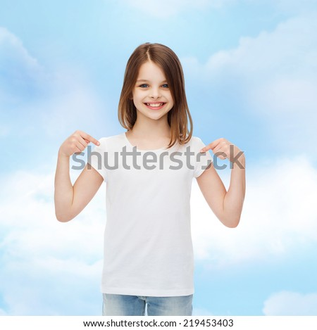 advertising, dream, childhood, gesture and people - smiling little girl in white t-shirt pointing fingers on herself over cloudy sky background