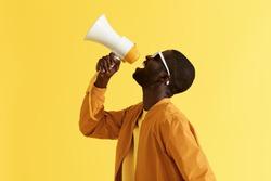 Advertising. Man screaming announcement in megaphone on yellow background. Portrait of african american male model in fashion wear using loud speaker in studio