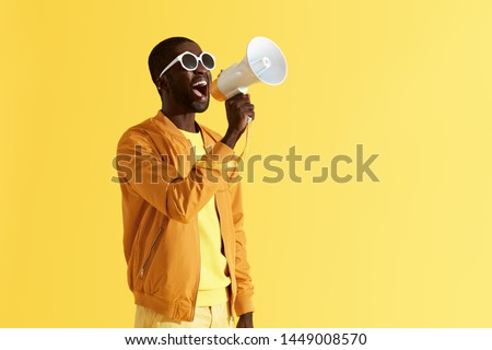 Photo of  Advertising. Man screaming announcement in megaphone on yellow background. Portrait of african american male model in fashion wear using loud speaker in studio