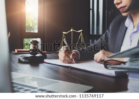 advice and justice concept. Justice scales, justice hammer and Litigation and Litigation document, female lawyer using pen point law book, working legal law with use laptop at  lawyer office.