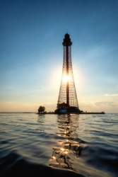 Adzhyholskyy mayak or Adziogol lighthouse also known as Stanislav range rear light in Dnieper estuary, Ukraine. Scenic sunset landscape with navigation construction, water, blue sky and sun