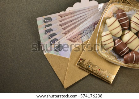 Aed one thousand uae dhs currency notes in a golden envelope with date chocolates along with it. Islamic festive gift or 'cash rewards' concept. #574176238