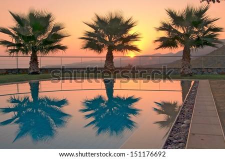 Aegean Sunrise - Summer sunrise over the Cretan mountains with palm trees reflecting in a pool in Malia, Crete