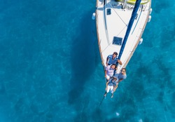 Aeiral view of Happy family with adorable daughter and son resting on a big yacht. Drone photography