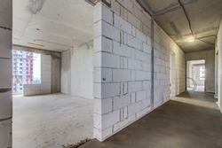 Aerated concrete blocks house corridor walls under construction ready for plastering and stucco. Corridor under construction. Mounting frame and ceiling. Light at the end of the tunnel. Unfinished