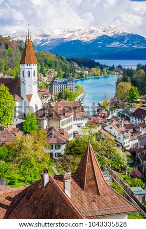 Aeria Scenery of Old Town Cityscape from Thun Castle and Alpine Mountain Range in Switzerland with Cloudy. Swiss Village among Swiss Alps. Scenic Landscape of Switzerland Country with Snowy Mountain.