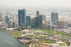Aerial above view of Sharjah city with beautiful park, mosque and high-rise buildings