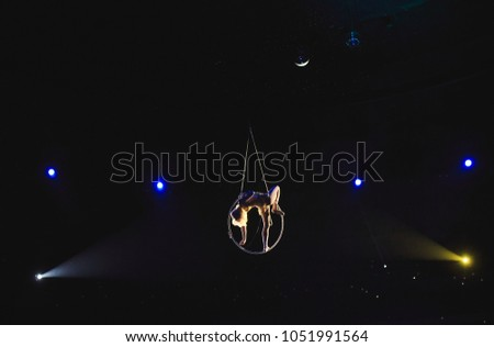 Aerial acrobat in the ring. A young girl performs the acrobatic elements in the air ring.
