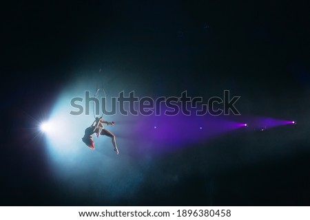 Aerial acrobat in the ring. A young girl performs the acrobatic elements in the air ring Stockfoto ©