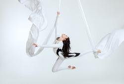 Aerial artistic acrobatics, a woman demonstrates poses.