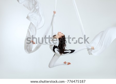 Aerial artistic acrobatics, a woman demonstrates poses.