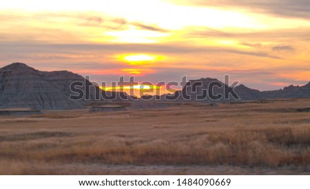 AERIAL: Beautiful endless sandstone formations and dry grass prairie at Badlands National Park at sunset. Amazing landscape with eroded rocky mountains rising out of vast grassland at reddish sunrise ストックフォト ©