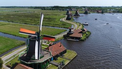 Aerial bird-eye photo of Zaanse Schans Zaandam flying past one of well-preserved historic windmills for tourists this is one of the most popular tourist attractions near Amsterdam Holland Netherlands