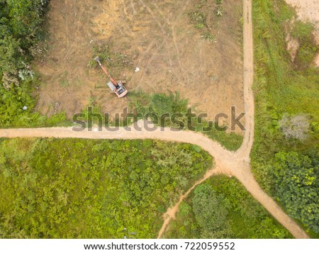 Aerial bird eye view of excavator clearing forest land for development. #722059552