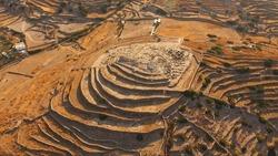 Aerial bird's eye photo of iconic prehistoric settlement of Skarkos, Ios island, Cyclades, Greece