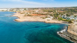 Aerial bird's eye view of Ammos tou Kambouri beach, Ayia Napa, Cavo Greco, Famagusta, Cyprus. Tourist attraction bay, rocky beach with golden sand, sunbeds, sea restaurant in Agia Napa from above.