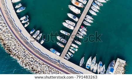 Aerial bird's eye view of Zygi fishing village port, Larnaca, Cyprus. Bird eye view of aligned fish boats moored in the harbour, docked yachts, pier, wave breaker rocks near Limassol city from above