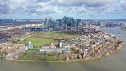 Aerial bird's eye view photo taken by drone from Greenwich park with views to Canary Wharf skyline with beautiful cloudy sky, Isle of Dogs, London, United Kingdom