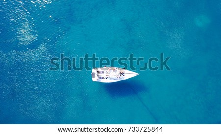 Aerial bird's eye view photo taken by drone of boat docked in caribbean tropical beach with turquoise - sapphire waters