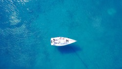 Aerial bird's eye view photo taken by drone of sailboat anchored in caribbean tropical beach with turquoise - sapphire waters
