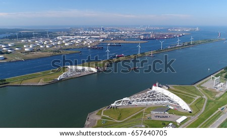 Aerial bird view photo Maeslantkering showing the large white arms of storm surge barrier part of Delta Works #657640705