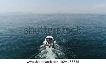 Aerial bird view picture motorboat cabin cruiser with sun tanning people on the stern of boat slow cruising over ocean water showing small waves from calm weather on beautiful summer day