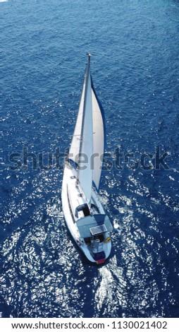 Aerial birds eye drone view of luxury sailboat in deep blue water, island of Santorini, Cyclades, Greece