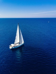 Aerial birds eye view from drone of white yacht in deep blue sea