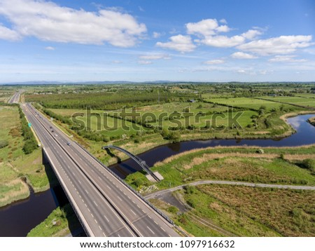 aerial birds eye view of a busy motorway with bridge crossing a river of water and railway track. ennis county clare ireland.