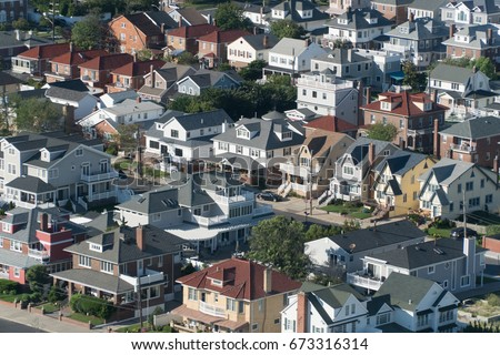 Aerial birds eye view of expensive ocean side real estate houses on bright summer day. Neighborhood of luxury beach front homes