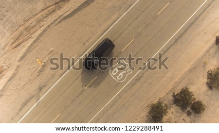 AERIAL: Black SUV car driving along historic Route 66 through the vast desert. People traveling, road trip on empty countryside road through America on sunny summer vacation